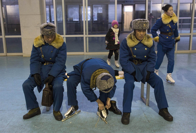 An off duty North Korean traffic policeman laces up ice skates as his colleagues sit near by at an ice skating rink in Pyongyang, North Korea Friday, January 11, 2013. (Photo by David Guttenfelder/AP Photo)