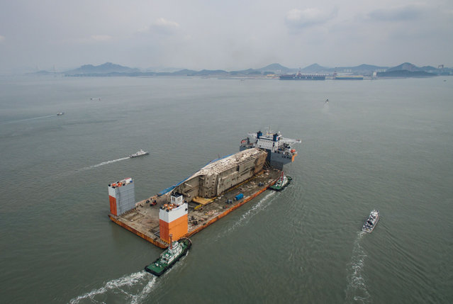This aerial general view shows the wreck of the Sewol ferry mounted on a semi- submersible barge during its arrival at a port in Mokpo on March 31, 2017. The salvaged wreck of South Korea' s Sewol ferry finally reached port on March 31, nearly three years after setting out on a doomed voyage that killed more than 300 people. (Photo by Ed Jones/AFP Photo)