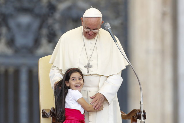 A child smiles as she embraces Pope Francis during an audience for the participants of the Convention of the Diocese of Rome in St. Peter's square at the Vatican City, June 14, 2015. (Photo by Giampiero Sposito/Reuters)