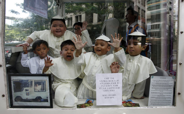 Children wearing Pope's cassocks ride a Popemobile that was used by Pope John Paul II in his 1995 visit to Manila, during a parade in Quezon city, Metro Manila April 27, 2014. Pope John XXIII, who reigned from 1958 to1963 and called the modernising Second Vatican Council, and Pope John Paul II, who reigned for nearly 27 years before his death in 2005 and whose trips around the world made him the most visible pope in history, will be declared saints by Pope Francis at an unprecedented twin canonisation on Sunday. (Photo by Erik De Castro/Reuters)