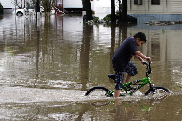 Angel Garcia rides his bike through flood waters after heavy rainfall caused major flooding on Monday, April 7, 2014, in Pelham, Ala. Severe thunderstorms crawled across the Southeast on Monday, dumping heavy rains and causing flash flooding in central Alabama, where crews in small boats and military trucks had to rescue dozens of people from their homes and cars. The storms walloped Mississippi on Sunday and spread overnight into Alabama and Georgia. (Photo by Butch Dill/AP Photo)