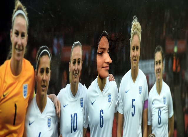 A girl poses for a photograph in a cut out of the England team during the FA Girls and West Riding County FA Football Festival  on July 9, 2015 in Keighley, England. (Photo by Nigel Roddis/The FA via Getty Images)