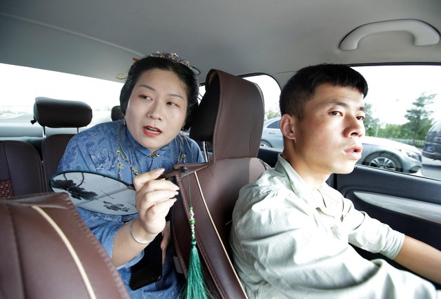 """Li Doudou, dressed in """"Hanfu"""", or Han clothing, speaks to a taxi driver on her way to attend a performance of the """"guqin"""" traditional musical instrument, an ancient seven-stringed zither, in Beijing, China, August 18, 2019. (Photo by Jason Lee/Reuters)"""