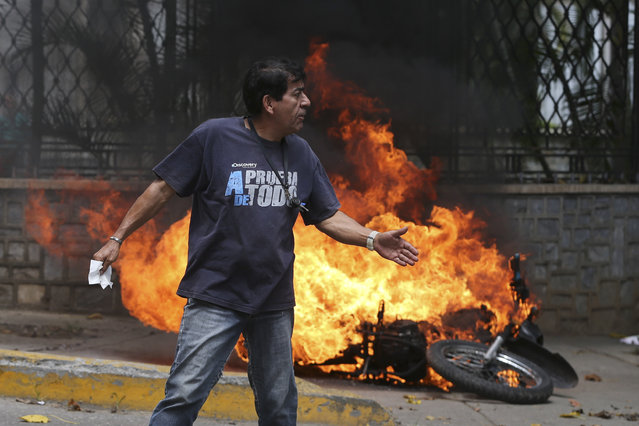 """A man walks past a burning motorbike set on fire by protesters during an opposition march in Caracas, Venezuela, Wednesday, April 19, 2017. Opponents of President Nicolas Maduro called on Venezuelans to take to the streets on Wednesday for what they dubbed the """"mother of all marches"""" against the embattled socialist leader. Government supporters are holding their own counter demonstration. (Photo by Fernando Llano/AP Photo)"""