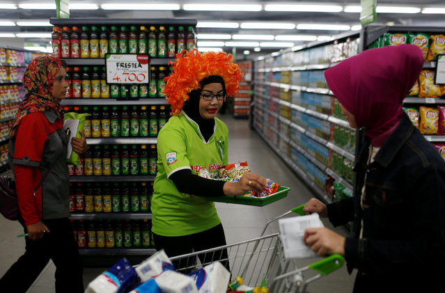 A sales promoter (C) offers a food sample to a customer at Foodmart Fresh supermarket in Jakarta, Indonesia, May 4, 2016. (Photo by Reuters/Beawiharta)