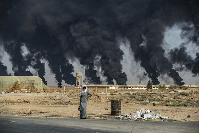 """A woman stands along the side of a road on the outskirts of the town of Tal Tamr near the Syrian Kurdish town of Ras al-Ain along the border with Turkey in the northeastern Hassakeh province on October 16, 2019, with the smoke plumes of tire fires billowing in the background to decrease visibility for Turkish warplanes that are part of operation """"Peace Spring"""". (Photo by Delil Souleiman/AFP Photo)"""