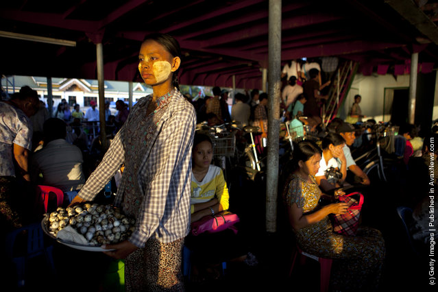 Burmese pack a Yangon ferry heading home during rush hour as a woman sells boiled bird eggs in Yangon, Myanmar
