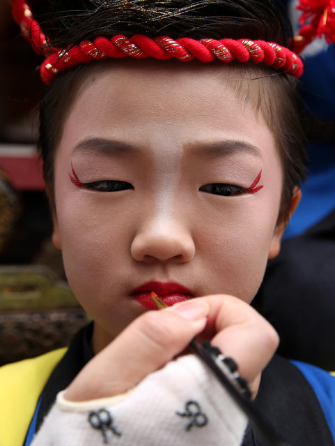 Japanese flower cart girl make-up applied to her face during the Mikuini annual festival on May 20, 2014 in Sakai, Japan. The annual festival takes place from May 19-21 and is attended by thousands of visitors. During the festival people dressed in traditional Japanese costumes pull carts carrying 6 meter high dolls of Japanese historical figures through the narrow streets. The origins of the festival are unclear but its history can be traced back more than 250 years. (Photo by Buddhika Weerasinghe/Getty Images)