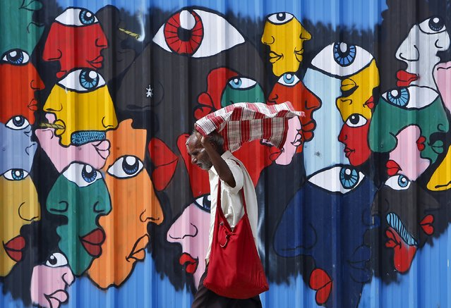 A commuter adjusts his scarf as he walks past a mural along a roadside in New Delhi, India, July 16, 2015. (Photo by Anindito Mukherjee/Reuters)