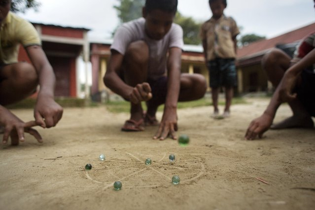 In this Tuesday, July 7, 2015 photo, children play marbles in the village of Mayong, east of Gauhati, India. (Photo by Anupam Nath/AP Photo)