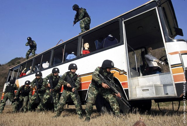 Chinese armed police officers surround a coach during a simulated terrorist hijacking as part of an anti-terror drill by the Shanghai Armed Police Corps