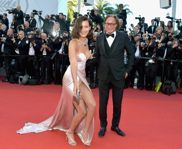 "Bella Hadid smiles as she picks up a camera battery which a photographer dropped on the red carpet, before giving it back as she attends the ""Ismael's Ghosts (Les Fantomes d'Ismael)"" screening and Opening Gala during the 70th annual Cannes Film Festival at Palais des Festivals on May 17, 2017 in Cannes, France. (Photo by Pascal Le Segretain/Getty Images)"