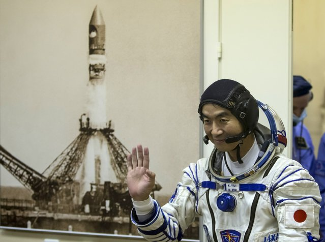 The International Space Station (ISS) crew member Kimiya Yui of Japan waves after donning his space suit at the Baikonur cosmodrome, Kazakhstan, July 22, 2015. (Photo by Shamil Zhumatov/Reuters)