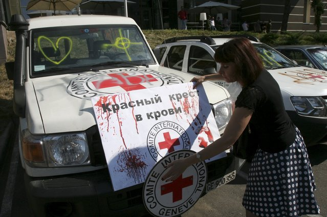 """A demonstrator adjusts a placard reading """"Red Cross is in blood"""" on a vehicle of the Red Cross during a protest to demand what protesters say is true information from the Organisation for Security and Co-operation in Europe (OSCE) about the shelling in Donetsk, Ukraine, July 23, 2015. (Photo by Igor Tkachenko/Reuters)"""