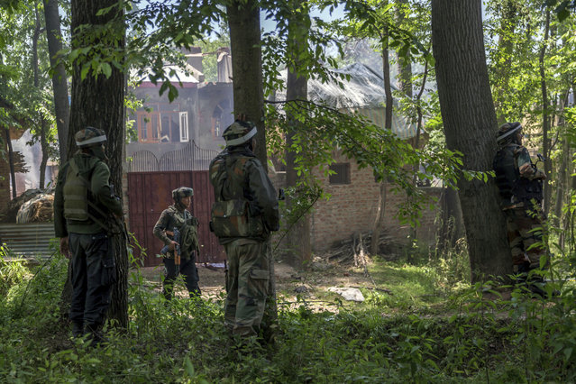 Indian army soldiers take position near the house where two suspected militants were killed in a gunbattle at Saimoh village, in Tral area, about 45 Kilometres south of Srinagar, Indian controlled Kashmir, Saturday, May 27, 2017. Rebel leader Sabzar Ahmed Bhat and a fellow militant were killed after troops cordoned off the southern Tral area overnight following a tip that rebels were hiding there, police said. The gunbattle ended later Saturday and soldiers recovered the bodies of two militants. (Photo by Dar Yasin/AP Photo)