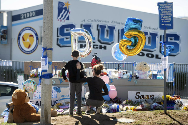 Michelle Bosshard and her 9-year-old son Lucas visit a memorial, Monday, November 18, 2019, for two students killed during a shooting at Saugus High School in Santa Clarita, Calif., days before. The Bosshards, who live in the neighborhood, know a handful of kids who were hiding during the shooting. The students will return to school on Dec. 2. (Photo by Sarah Reingewirtz/The Orange County Register via AP Photo)