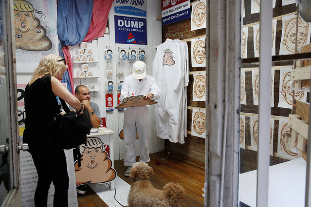 A woman inspects artwork referencing U.S. Republican presidential candidate Donald Trump made by the artist Hanksy and being sold at a temporary store in New York, U.S., June 4, 2016. (Photo by Lucas Jackson/Reuters)