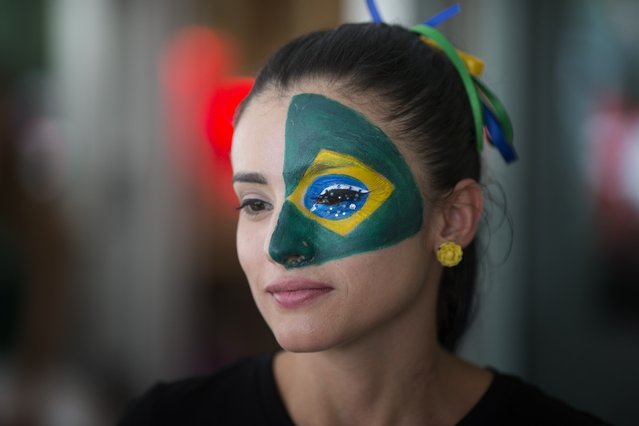 Soccer fan Marcella Guevara, with her face painted, watches televised World Cup soccer action between Brazil and Croatia at the Kukaramakara cafe block party in Miami, Thursday, June 12, 2014. (Photo by J. Pat Carter/AP Photo)