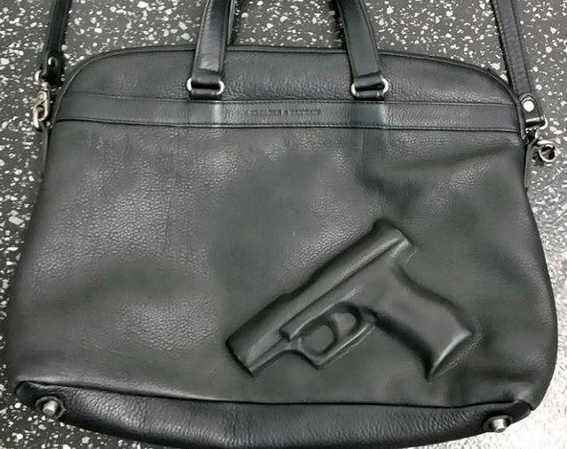 A handout picture made available by Bremen Police shows a handbag with an embossed gun laying on the floor at the airport in Bremen, Germany, July 31, 2015. The design of a woman's handbag roused suspicion at Bremen airport, with an official reportedly saying that such bags may not be used as hand luggage. (Photo by EPA/Bremen Police)