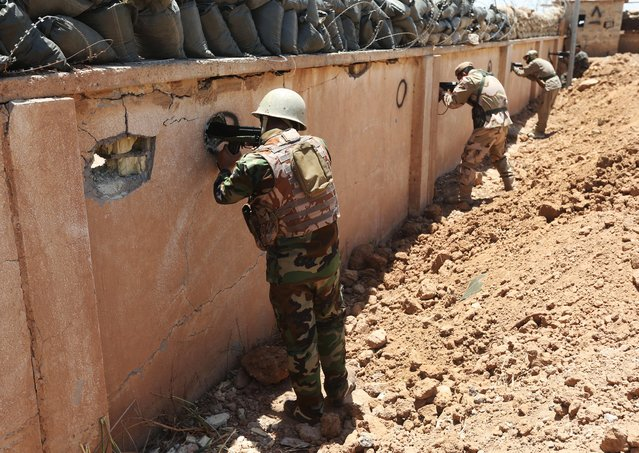 Kurdish peshmerga fighters take their positions behind a wall on the front line with militants from the al-Qaida-inspired Islamic State in Iraq and the Levant (ISIL), in Tuz Khormato, 100 kilometers (62 miles) south of the oil rich province of Kirkuk, northern Iraq, Wednesday, June 25, 2014. (Photo by Hussein Malla/AP Photo)
