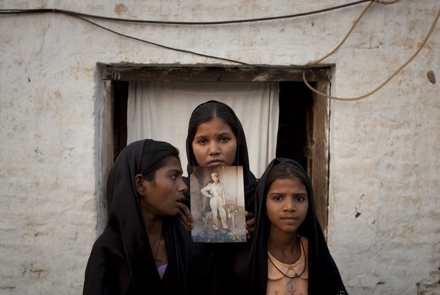 The daughters of Pakistani Christian woman Asia Bibi pose with an image of their mother while standing outside their residence in Sheikhupura located in Pakistan's Punjab Province, in this November 13, 2010 file photo. (Photo by Adrees Latif/Reuters)