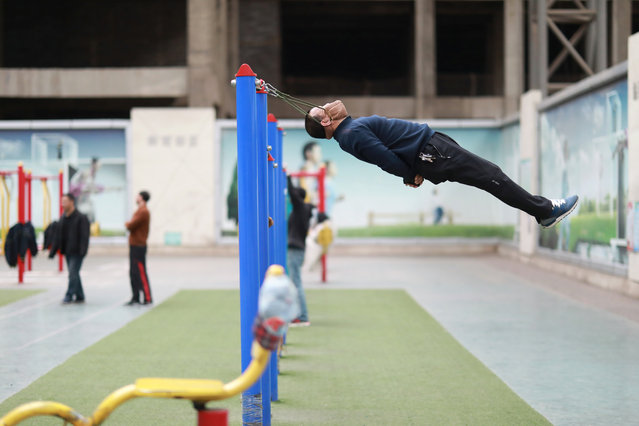 Sun Rongchun, 57, exercises with an improvised cervical traction device attached to a high bar at a sports complex in Shenyang, Liaoning province, China on April 9, 2019. (Photo by Sheng Li/Reuters)