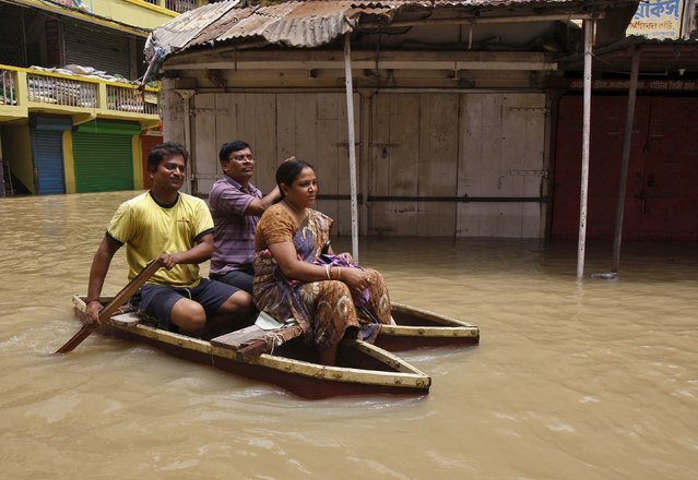 Flood-affected people use a boat as they move to safer grounds along a flooded street at West Midnapore district in West Bengal, India, August 4, 2015. (Photo by Rupak De Chowdhuri/Reuters)