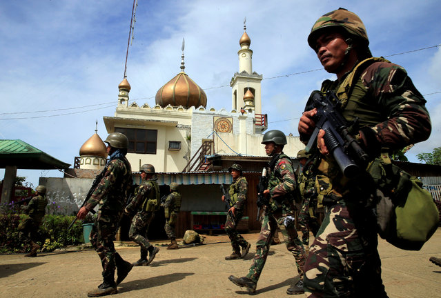 Government troops walk past a mosque before their assault with insurgents from the so-called Maute group, who have taken over large parts of Marawi City, southern Philippines May 25, 2017. (Photo by Romeo Ranoco/Reuters)