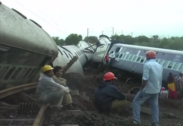In this image made from video, people gather by two derailed trains in Harda in Madhya Pradesh state, India, Wednesday, August 5, 2015. Two passenger trains derailed over a bridge in central India while crossing a track that was flooded by heavy monsoon rains, killing at a number of people, officials said Wednesday. (Photo via AP Video)