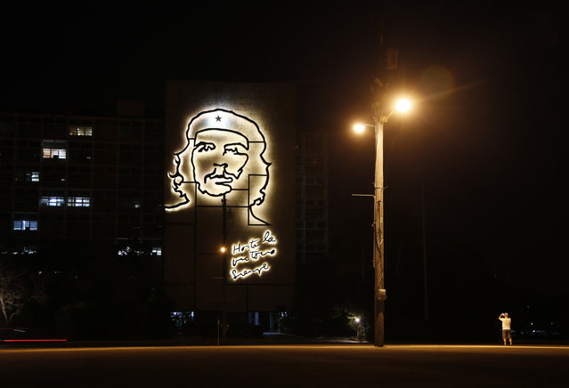 """A man takes pictures of an illuminated iron sculpture of Cuba's revolutionary hero Ernesto """"Che"""" Guevara on the Ministry of Interior building at Revolution Square in Havana, Cuba, Friday, April 10, 2015. (Photo by Desmond Boylan/AP Photo)"""