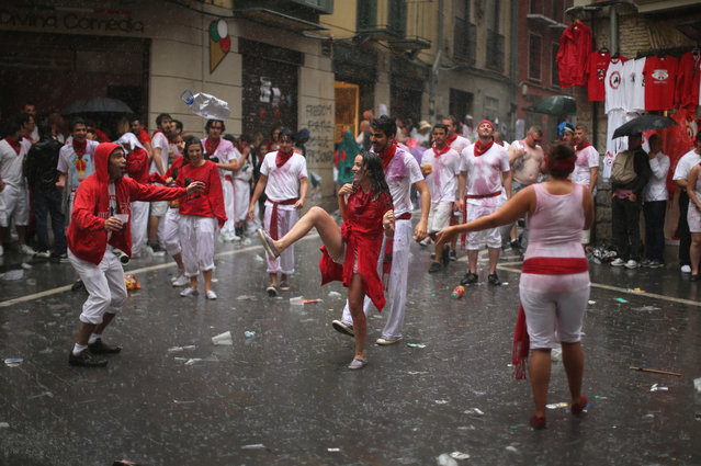 """Revellers dance in the rain after the opening and the firing of the """"Chupinazo"""" rocket which starts the 2014 Festival of the San Fermin Running of the Bulls on July 6, 2014 in Pamplona, Spain. The annual Fiesta de San Fermin, made famous by the 1926 novel of US writer Ernest Hemmingway entitled """"The Sun Also Rises"""", involves the daily running of the bulls through the historic heart of Pamplona to the bull ring. (Photo by Christopher Furlong/Getty Images)"""