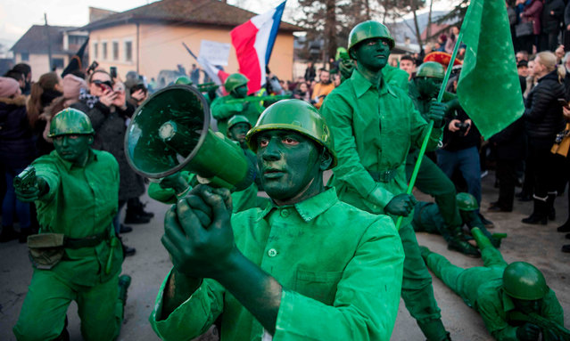 Masked revellers take part in a carnival procession through the south-western North Macedonian village of Vevcani, on January 13, 2020. The Vevcani carnival is 1.400 years old and is held every year on the eve of the feast of Saint Basil (January 14), which also marks the beginning of the New Year according to the Julian calendar, observed by the Macedonian Orthodox Church. (Photo by Robert Atanasovski/AFP Photo)