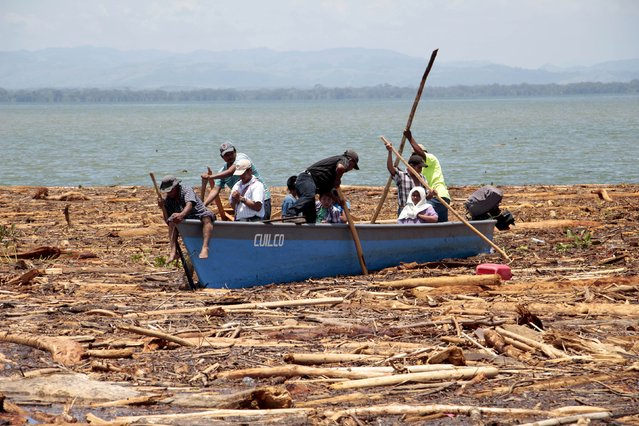 Villagers looks for missing people after heavy rains using sticks over a boat in Punta Caimanes, in the Izabal region, near Guatemala City, August 8, 2015. (Photo by Josue Decavele/Reuters)