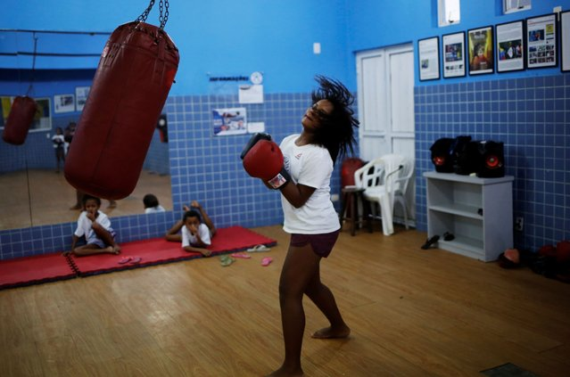 A girl practices with a punch bag during an exercise session at a boxing school, in the Mare favela of Rio de Janeiro. (Photo by Nacho Doce/Reuters)