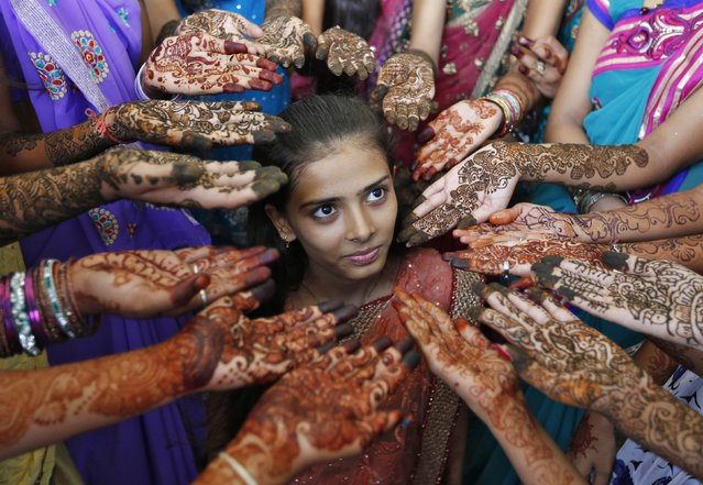 Schoolchildren show their hands decorated with henna paste during a henna competition to mark World Population Day in the western Indian city of Ahmedabad July 11, 2014. (Photo by Amit Dave/Reuters)