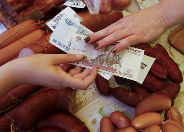 A vendor (R) takes Russian rouble banknotes from a customer buying sausage produced on a local private farm, at a street food market in the Siberian city of Krasnoyarsk, Russia, July 29, 2015. The Russian rouble opened 0.8 percent stronger against the dollar on Wednesday after the central bank said it stopped carrying out FX interventions from July 28 because of increased market volatility. (Photo by Ilya Naymushin/Reuters)