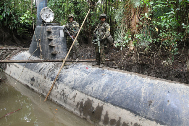Members of the Colombian Navy stand guard on top of a seized submarine built by drug smugglers in a makeshift shipyard in Timbiqui, department of Cauca February 14, 2011. Colombian authorities said the submersible craft was to be used to transport 8 tons of cocaine illegally into Mexico. (Photo by Jaime Saldarriaga/Reuters)