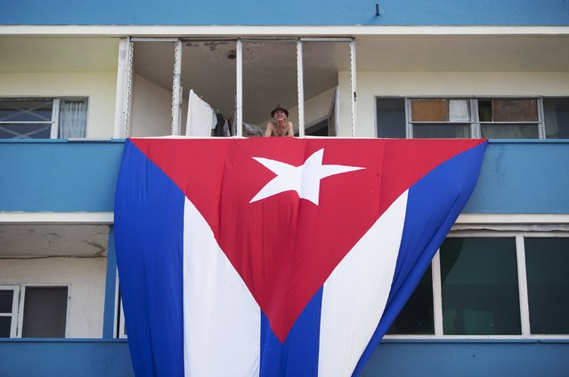 A man stands at his balcony above a Cuban flag, next to the U.S embassy building (not pictured), in Havana, Cuba August 11, 2015. U.S. Secretary of State John Kerry will travel to Cuba on August 14 to formally re-designate the U.S. Interests Section as the U.S. Embassy in Havana. (Photo by Alexandre Meneghini/Reuters)
