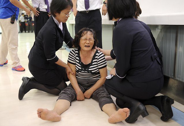 A relative of a passenger on board the crashed TransAsia Airways plane cries in Kaohsiung International Airport, southern Taiwan, July 23, 2014. A TransAsia Airways turboprop ATR-72 plane crashed on its second attempt at landing during a thunderstorm on Penghu, an island off Taiwan on Wednesday, killing 47 people and setting buildings on fire, officials said. (Photo by Reuters/Stringer)