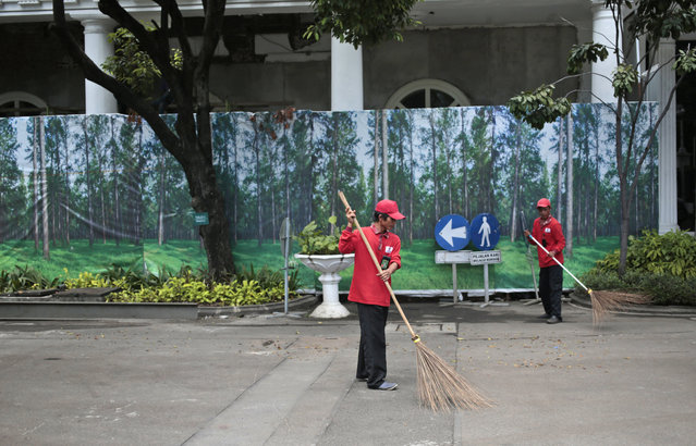 In this Wednesday, Oct. 26, 2016 photo, workers sweep dry leaves against the background of banners depicting a forest used to cover a construction site in Jakarta, Indonesia. One of the strange sights in Indonesia, an ecologically rich archipelago of more than 13,000 islands, is its capital's fondness for fake greenery at a time when the country is known for cutting down its precious tropical forests at a record rate. (Photo by Dita Alangkara/AP Photo)