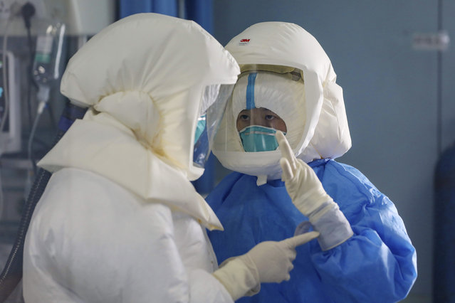 Medical staff work in the negative-pressure isolation ward in Jinyintan Hospital, designated for critical COVID-19 patients, in Wuhan in central China's Hubei province Thursday, February 13, 2020. China on Thursday reported 254 new deaths and a spike in virus cases of 15,152, after the hardest-hit province of Hubei applied a new classification system that broadens the scope of diagnoses for the outbreak, which has spread to more than 20 countries. (Photo by Chinatopix via AP Photo)
