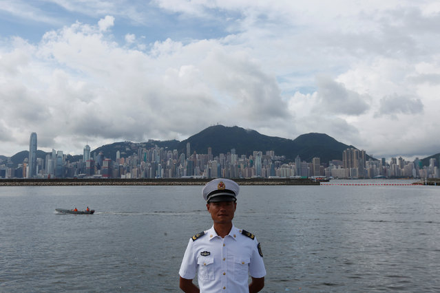 A People's Liberation Army naval soldier stands on a military vessel at a naval base with a Hong Kong skyline at background, during an open day celebrating the 19th anniversary of Hong Kong's handover to Chinese sovereignty from British rule, in Hong Kong July 1, 2016. (Photo by Bobby Yip/Reuters)
