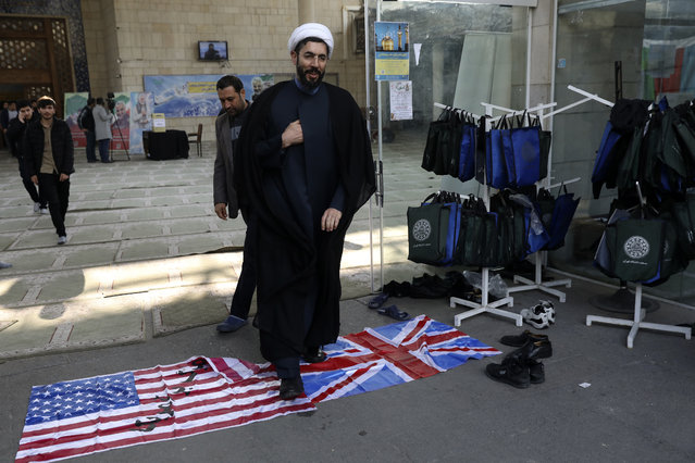 A cleric walks on the U.S. and British flags while leaving a gathering to commemorate the late Iranian Gen. Qassem Soleimani, who was killed in Iraq in a U.S. drone attack on January 3, and victims of the Ukrainian plane that was mistakenly downed by the Revolutionary Guard last Wednesday, at the Tehran University campus in Tehran, Iran, Tuesday, Jan. 14, 2020. (Photo by Vahid Salemi/AP Photo)