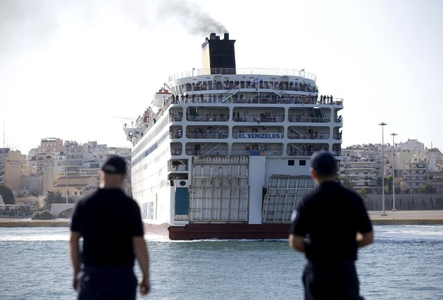 """Policemen watch the arrival of """"Eleftherios Venizelos"""" passenger ship, carrying hundreds of Syrian refugees onboard at the port of Piraeus near Athens, Greece, August 20, 2015. (Photo by Stoyan Nenov/Reuters)"""