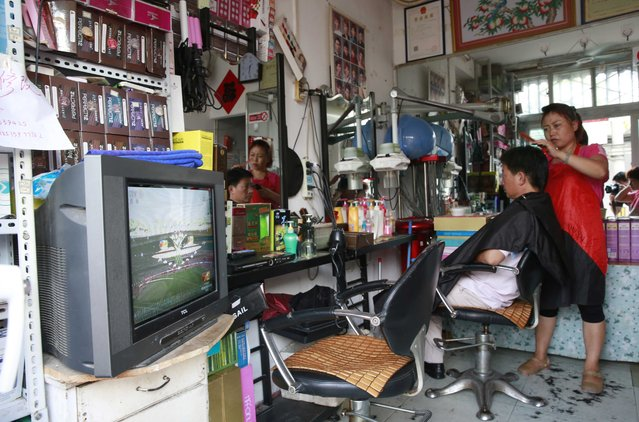 The opening ceremony of the 15th IAAF World Championships at the National Stadium is shown on a television in a barber's shop in Beijing, China August 22, 2015. (Photo by Kim Kyung-Hoon/Reuters)