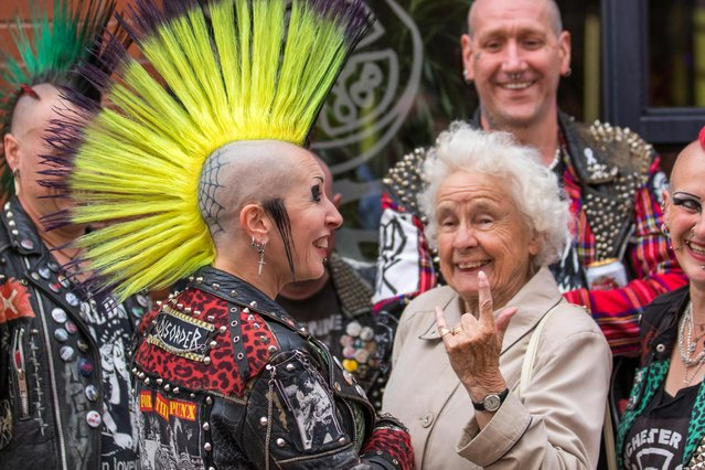 Irene Bowker, 88 years old at the Punk Rebellion festival at The Winter Gardens, talks to a woman with a tatooed head and mohican haircut in Blackpool, Lancashire, UK on August 6, 2015. A clash cultures at the famous seaside town of Blackpool as punks attending the annual Rebellion festival at the Winter Gardens come shoulder to shoulder with traditional holidaymakers. (Photo by MediaWorldImages/Alamy Stock Photo)
