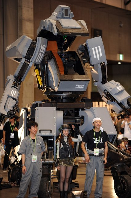 """Engineers Wataru Yoshizaki (L), Mitsugoro Kurata (R) and pilot Anna (C) pose in front of Japanese electronics company Suidobashi Heavy Industry's newly unveiled robot """"Kuratas"""" at the Wonder Festival in Chiba, suburban Tokyo on July 29, 2012. The Kuratas robot, which will go on sale with a price tag of one million USD, measures four meters in height, weighs four tons and has four wheeled legs that can either be controlled remotely through the 3G network or by a human seated within the cockpit."""