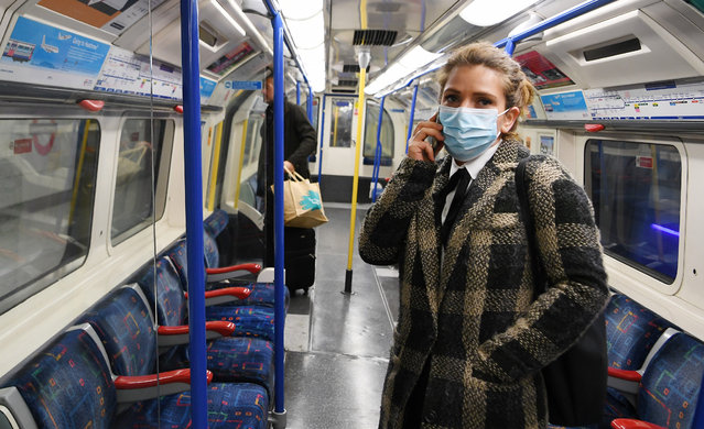A woman wears a protective mask aboard an Underground train in London, Britain, 14 March 2020. The British government is considering bann​ing mass gatherings due to the Coronavirus. (Photo by Andy Rain/EPA/EFE)