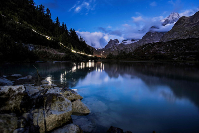 In this long exposure photo, lights of ultra- trailers competing illuminate the way past the Combal lake, on September 2, 2017 in Courmayeur, Italy, during the 15 th edition of the Mount Blanc Ultra Trail (UTMB), a 170 km race around the Mont Blanc crossing France, Italy and Switzerland. (Photo by Jeff Pachoud/AFP Photo)