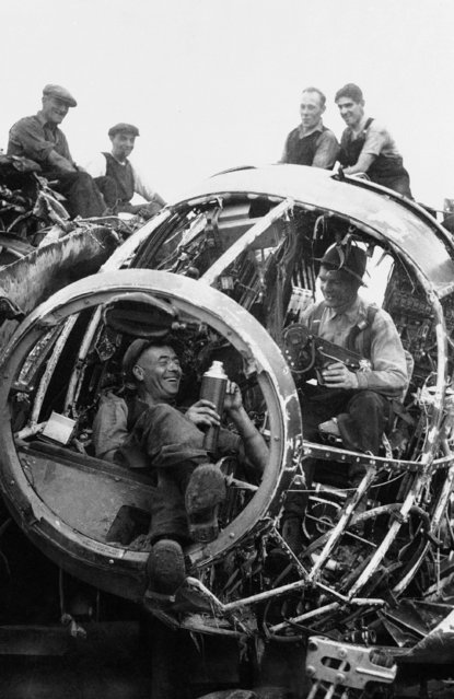 British workmen, employed in the reclamation of materials salvaged from German raiders which have been shot down over England, are eating lunch in the nose section of a raider in the salvage yard, August 27, 1940. (Photo by AP Photo)